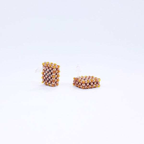 Kolczyki w kształcie bloczków wykonane z koralików w kolorze złotym, miodowym pokazują gdzie jest sztyft